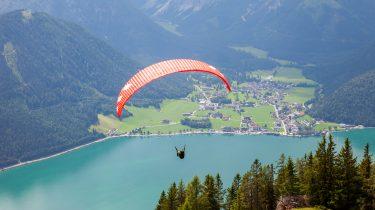 Ein Paragleiter schwebt hoch über dem Achensee. © ServusTV - DMG